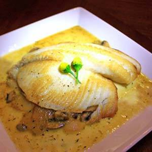 Pangasius Fish glazed with lemon on a plate.